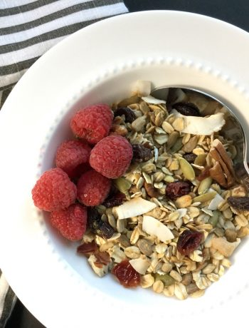 hearty granola with raspberries in a bowl with a spoon and striped napkin