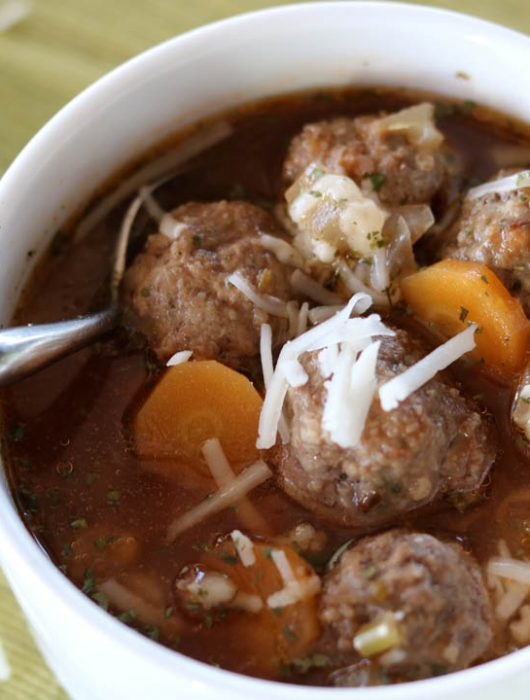 Italian meatball soup in a mug showing meatballs and carrots with shredded Parmesan cheese and a spoon.