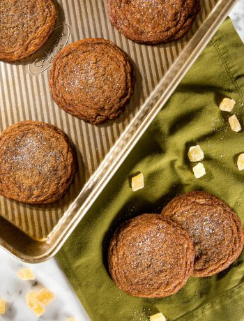 Molasses sugar cookies on a baking sheet with crystalized ginger and cookies on a napkin