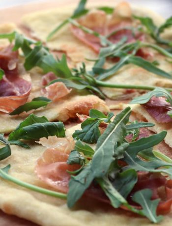 Teakerne Arm pizza with arugula and prosciutto served on a wooden cutting board.