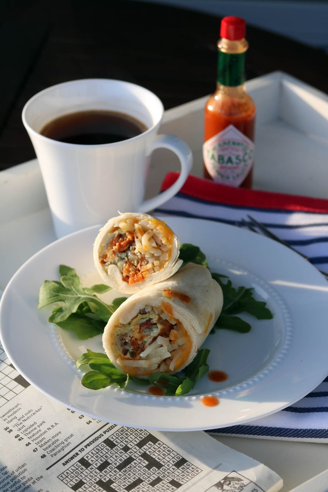 Breakfast burritos to grab-and-go on a tray on plate with cup of coffee and hot sauce on top of crossword puzzle.