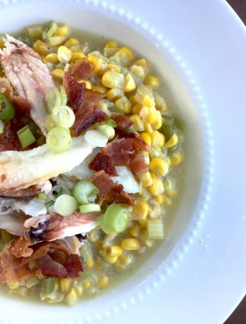 A white-rimmed bowl filled with fresh corn + crab chowder, garnished with bacon, green onions and a chunk of Dungenesss crab.