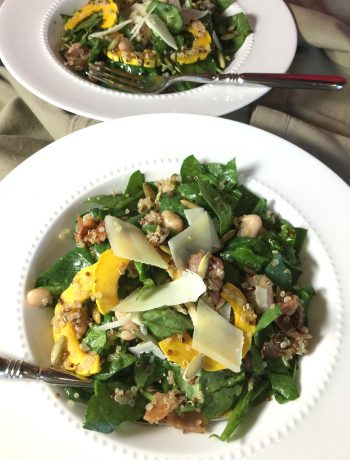 winter squash, spinach and prociutto salad arranged in two white bowls with forks in place.