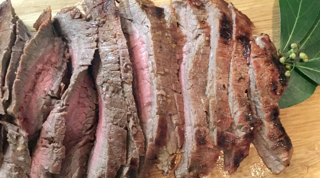 Sliced marinated flank steak cooked to medium rare and presented on a wooden cutting board.