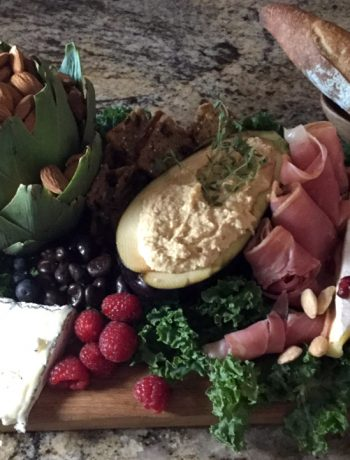 Rustic appetizer tray with an artichoke bowl, hummus, cheese, rustic baguette and berries.