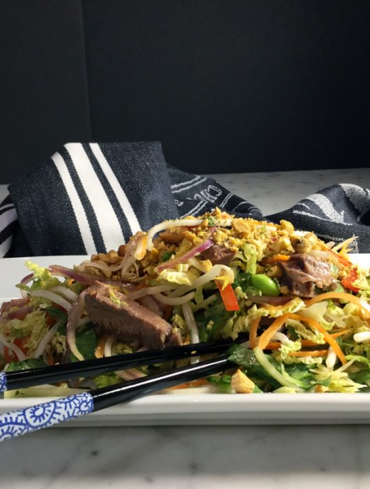 Flank steak salad plated with chopsticks sitting by a black and white napkin.