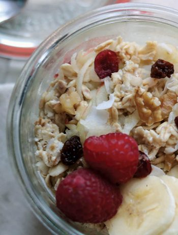 A class jar filled with swiss muesli topped with bananas, walnuts, raspberries and raisins, sitting on napkin and spoon at the side.