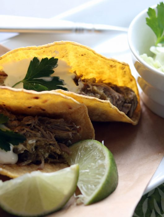 Two corn tortillas filled with pulled pork topped with sour cream and cilantro, zesty slaw on the side.