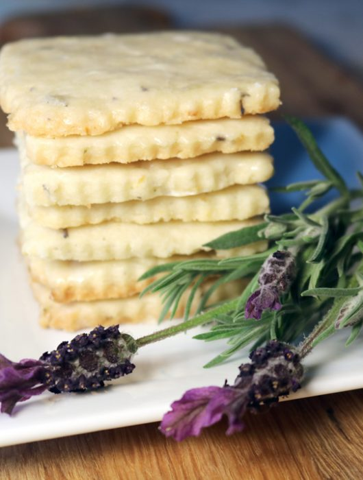 A stack of lorelle's lavender shortbread cookies on a square plate with several sprigs of lavender.