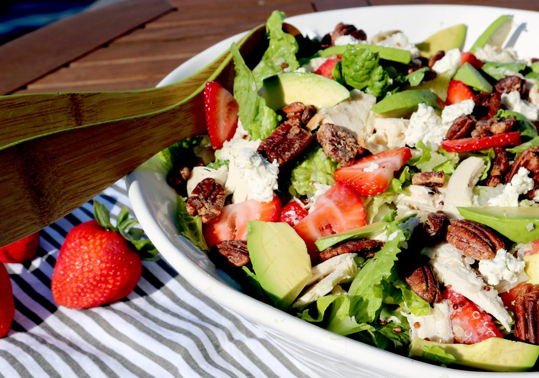 strawberry chicken salad in a bowl showing strawberries, avocado, chicken, pecans on a striped towel.
