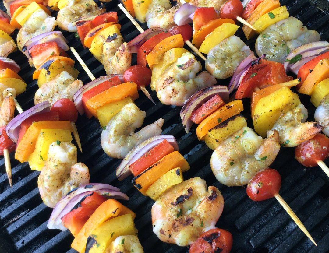 Caribbean shrimp kebobs on the grill threaded with shrimp, bell peppers, red onion and cherry tomatoes.