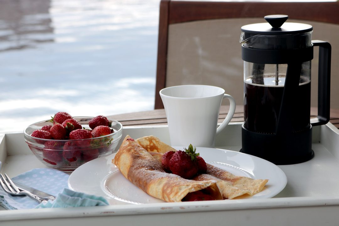 Crepes on a plate topped with strawberries along side a french press and mug of coffee.