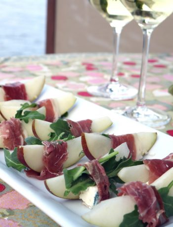 pear+ blue cheese appetizers on a white platter sitting on a table with two glasses of white wine.