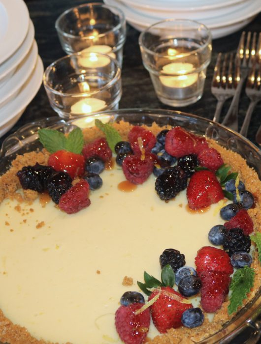 simply delicious key lime pie served in a glass pie pan with glazed strawberries, blueberries, blackberries and mint leaves.