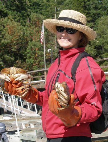 Carol in a red jacket and sun hat holding her dungeness crab catch at the dock.