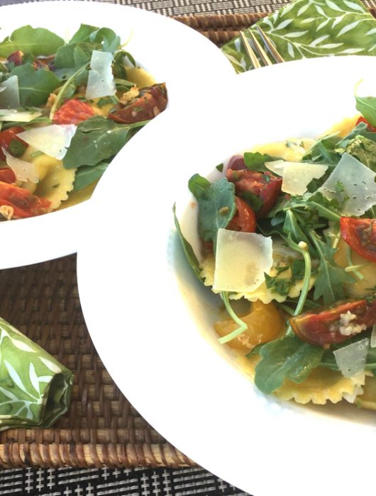 Two white bowls sitting on green and white napkins filled with raviola, arugula, roasted tomatoes and shaved Parmesan cheese.