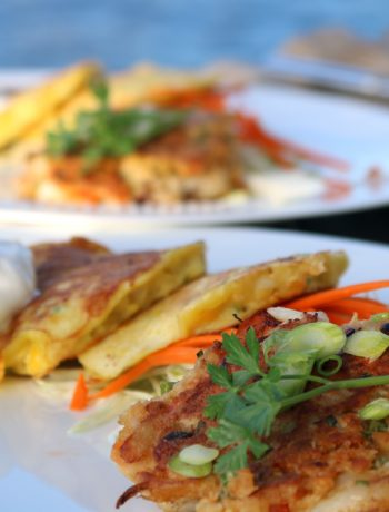 Plated with crab cakes are twofresh corn fritters and some limes wedges.