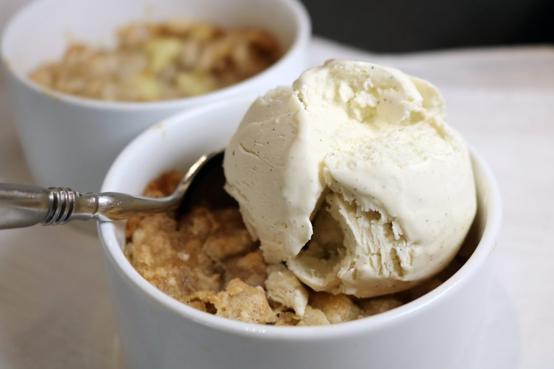Two apple tortes baked in ramekins with the front dessert topped with melting vanilla icecream. A spoon is in the dessert ready for a bite.