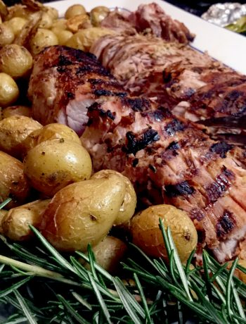 A platter with grilled rosemary pork tenderloinsloin nestled with roasted potatoes and a sprig of rosemary garnish.