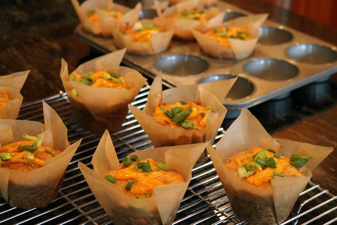 Savory corn muffins in parchment wrapped cups sitting on a cooling wrack with half left in muffin tins.