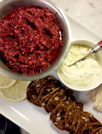 Cranberry salsa with whipped cream cheese and a red striped spreader on a white tray with two types of crackers.