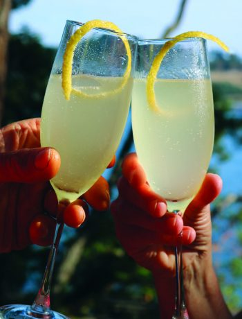 Two chilled flutes of French 75 cocktails with a twist of lemon in a toast.