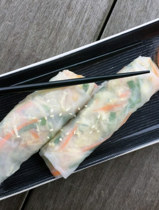 Two vietnamese spring rolls on a rectangle plate with sweet chili sauce and chopsticks on the side.