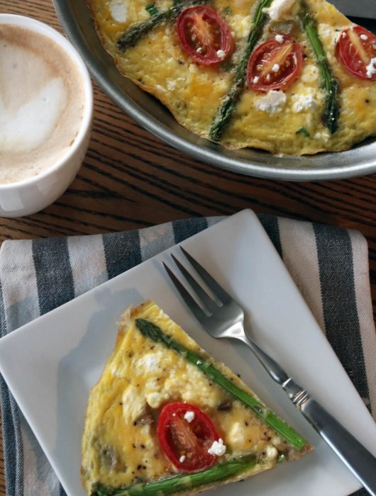 asparagus + goat cheese frittata slice on a plate with a fork and a latte and fritatta pan in the corner