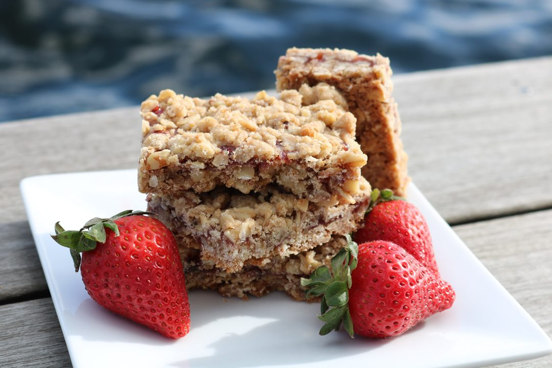 Jammy oatmeal bars sitting on a square plate garnished with three strawberries with water in the background.