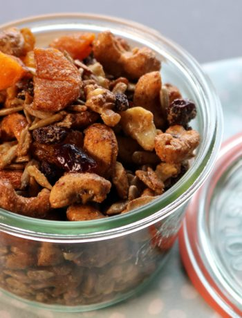 A glass jar with the lid on the side filled with sweet and salty trail mix of dried apricots, cashews, raisins sitting on a blue napkin.