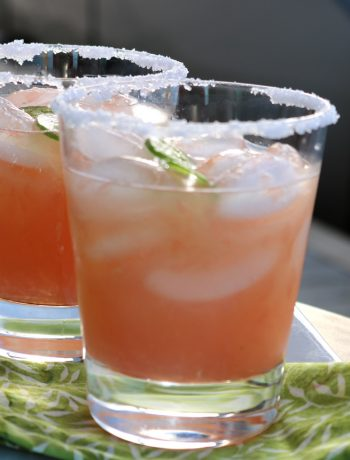 Two glasses of grapefruit jalapeno margaritas with salted rims sitting on a green napkin.