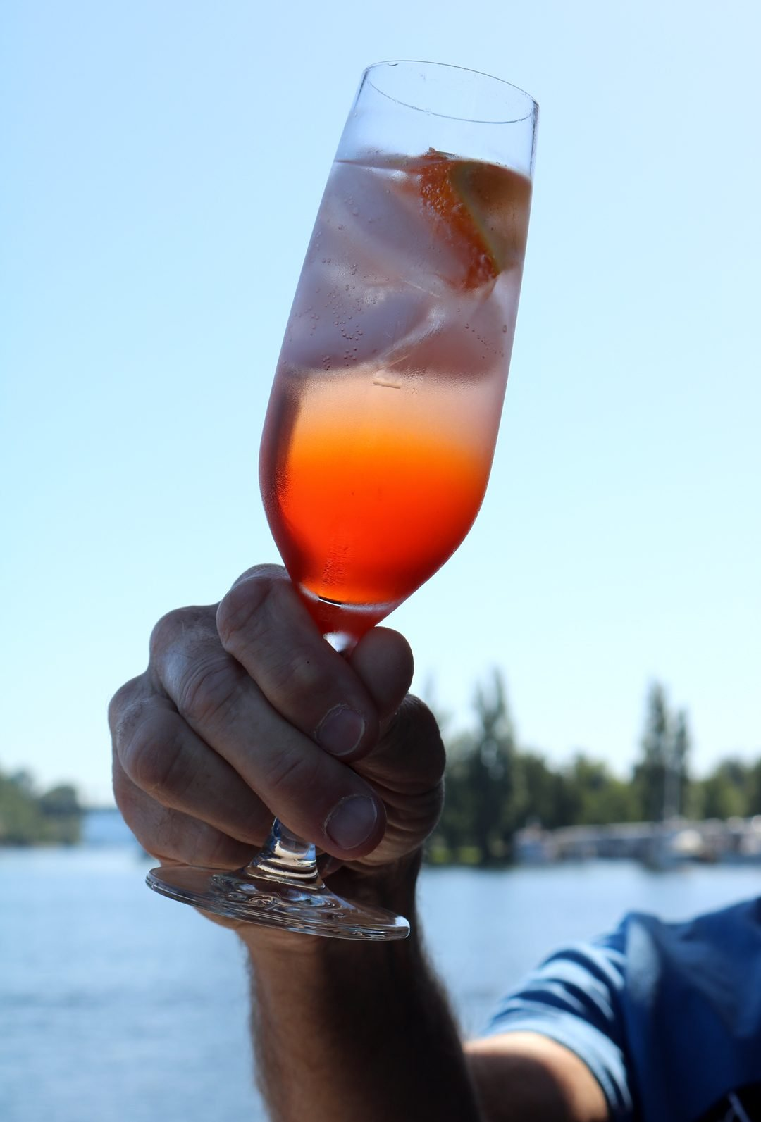 A chilled flute of aperol spritz held in the air with a water scene in the background.