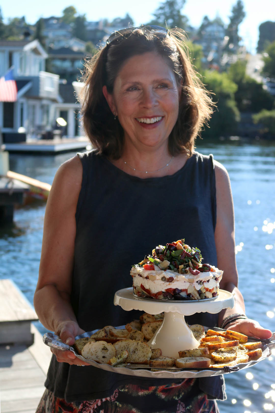Smiling woman at the water's edge,holding italian torte with crisp baguette slices on a tiered platter.