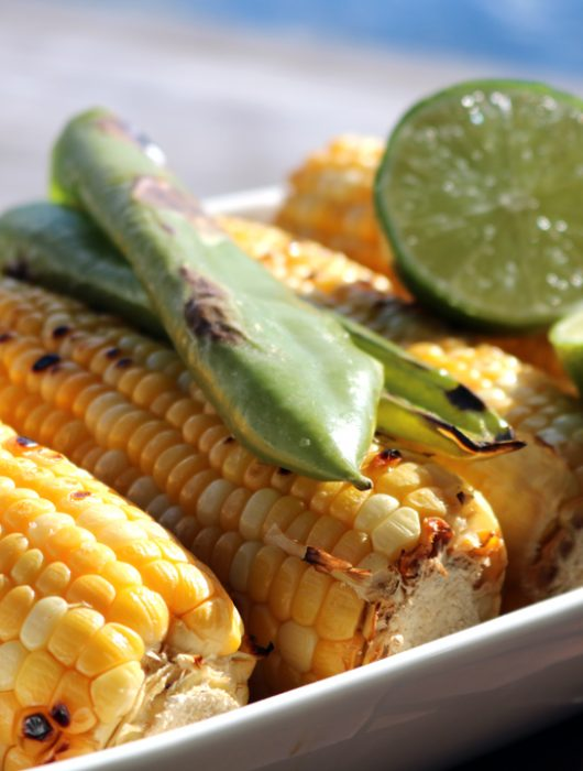 A square serving bowl holding grilled corn and peppers with a lime just off the grill.