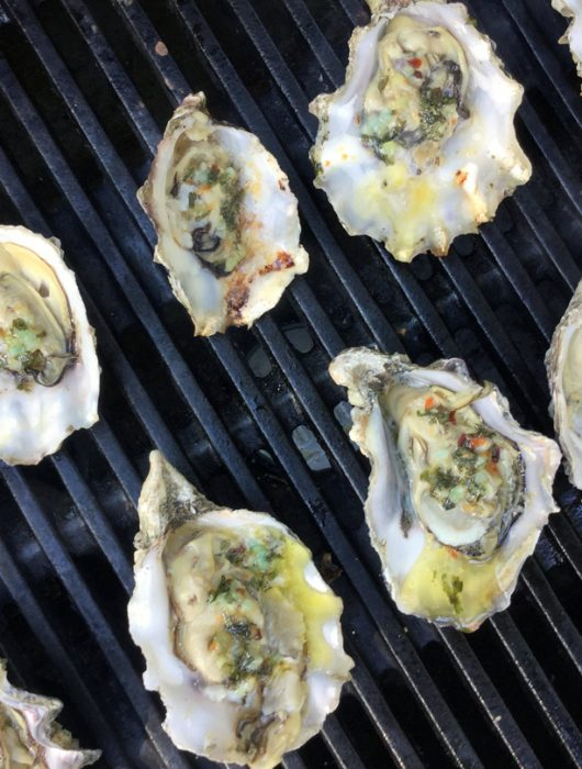 Fresh oysters on the grill with chopped parsley, lemon zest, butter, garlic, salt, and fresh pepper.