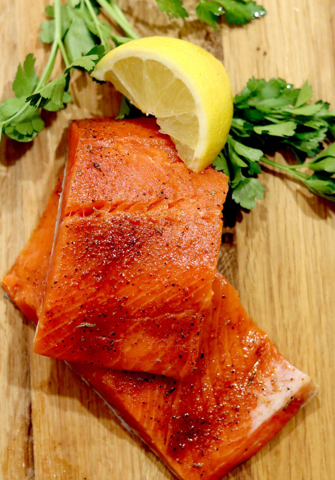 Sliced and sprinkled with rub, sockeye salmon ready for the grill. Lemon and parsley on the side.