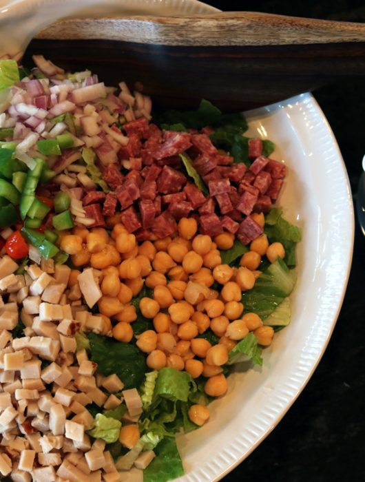 Madrona chopped salad arranged in a large shallow bowl with a pitcher of dressing on the side.