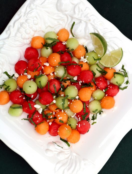 A square platter holding a melon medley of cantelope, watermelon, honeydew with a mint chiffonade and lime slices.