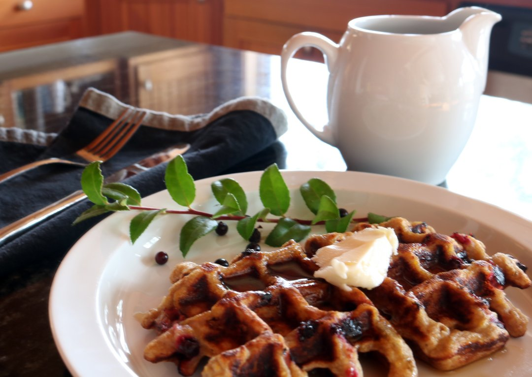 Wild huckleberry waffle soaked in syrup with a huckleberry sprig on the side, napkin and syrup pitcher behind the plate.