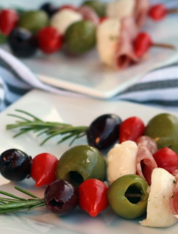 antipasto rosemary twig appetizers have olives, mozzarella balls, salami, and teadrop peppers threaded on a rosemay twig on square plates sitting on a striped napkin.