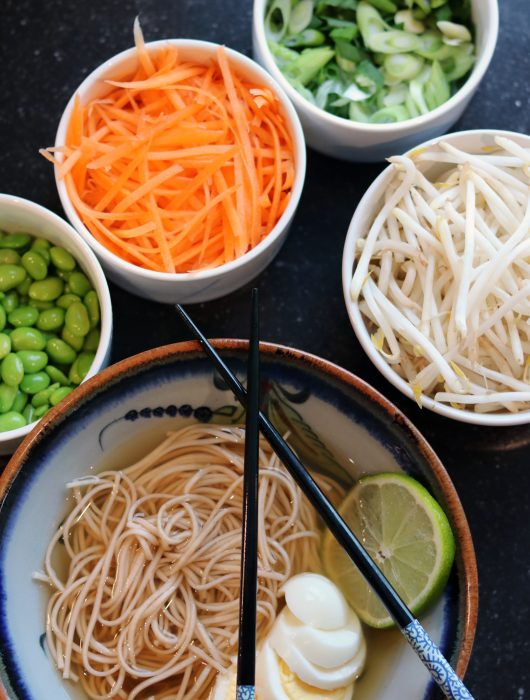chinese egg noodle bowl with hardboiled eggs, shredded carrots, bean sprouts, green onions and peas, garnished with lime slices and chop sticks