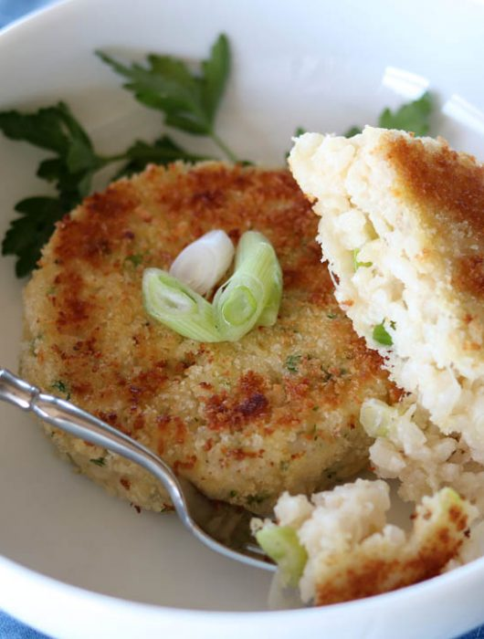 Two, creamy crispy risotto cakes in a bowl with a fork bite, garnishes with a sprig of parsley.