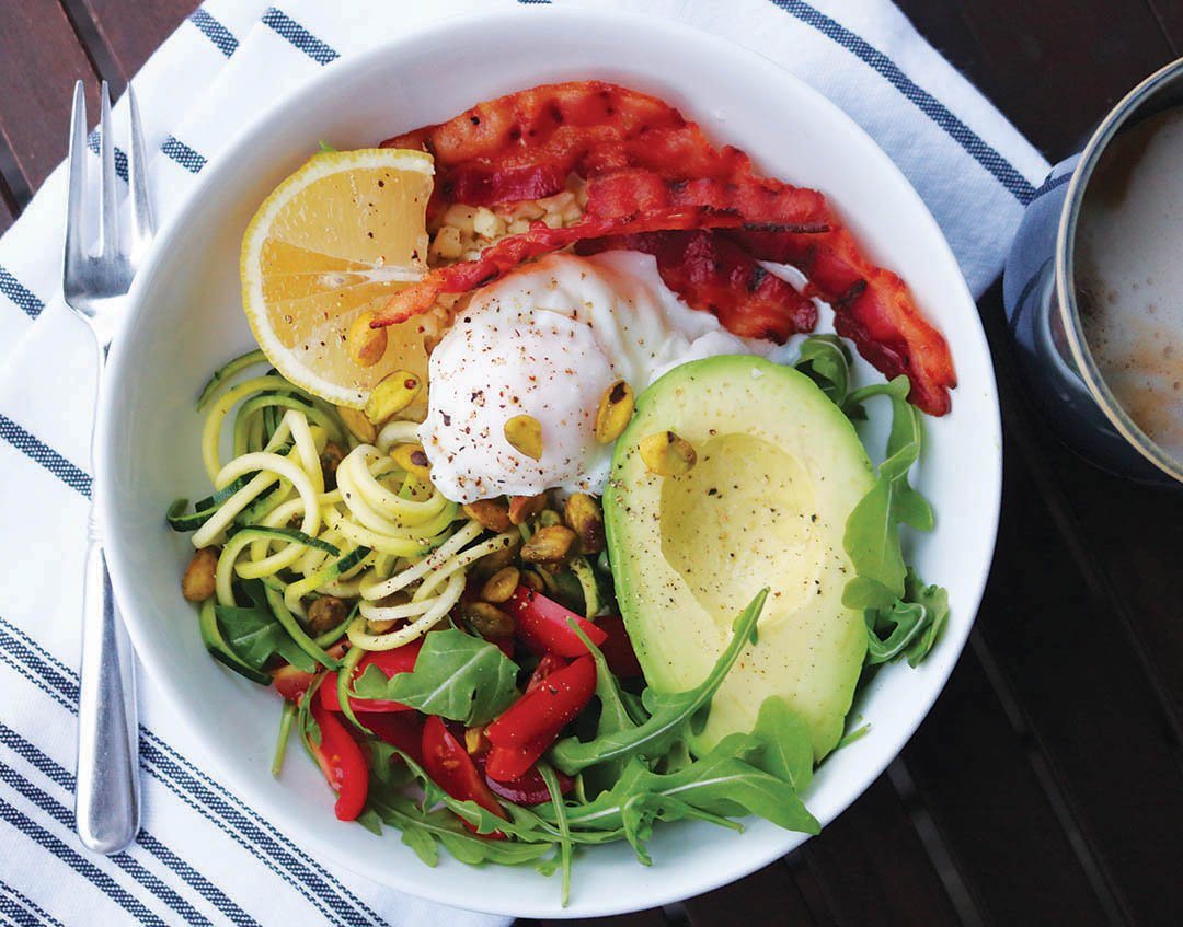 Nourishing breakfast bowl with avocado, poached eggs, bacon and veggies in a laarge bowl.