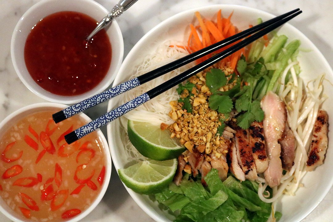 vietnamese noodle bowls salad bar with grilled chicken, shredded carrots, green onions and rice noodles