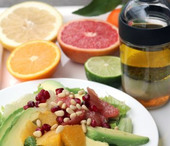 A salad plate with greens, orange and grapefruit sections, avocado slices, pomegranate seeds and pinenuts. Lemon poppy seed dressing in a jar and cut citrus fruits in the background.