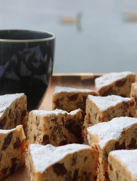 Apricot and date triangles on a wooden tray with a charcoal gray mug of tea and Canadian geese floating in the background.