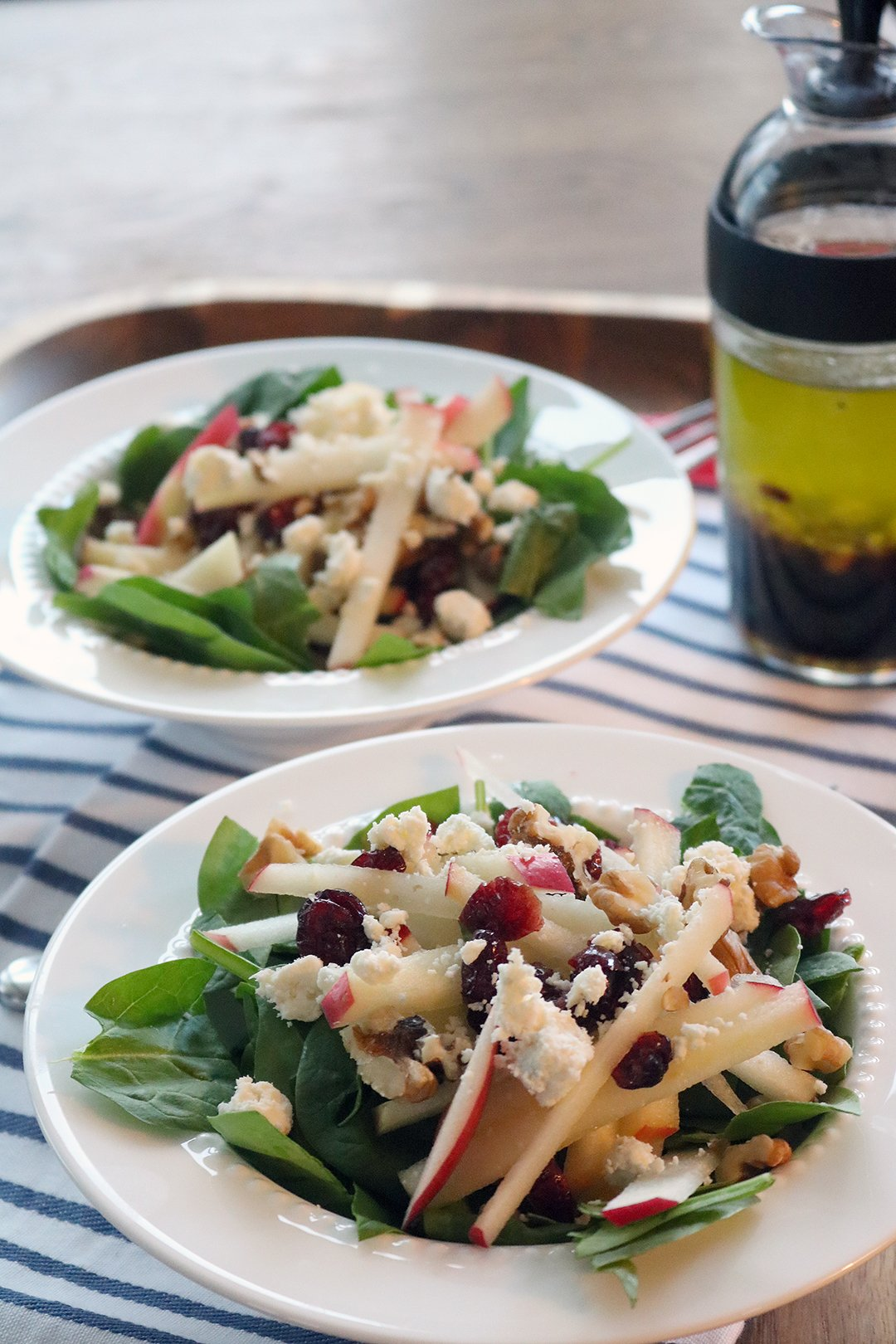 Two salad plates on a striped napkin with salad dressing behind. Apple sticks, dried cranberries, gorgonzola cheese and candied walnuts.