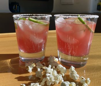 Two salt rimmed old fashioned glasses with hibiscus margaritas on ice sitting on a table with popcorn.