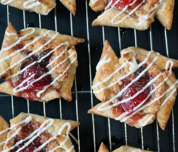 Four strawberry + almond breakfast pastries cooling on a baking rack sitting on a black cutting board, drizzled with glaze.