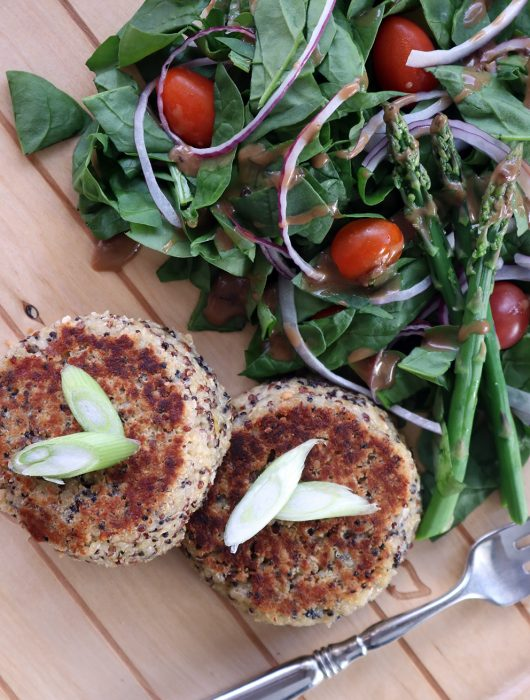 Quinoa cakes on a tray with a fork alongside a chopped spinach salad with asparagus spears.